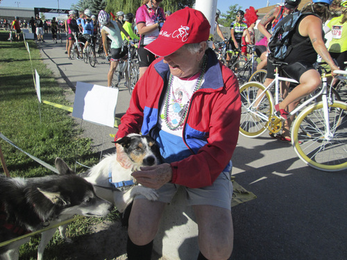 Kristen Moulton | Salt Lake Tribune  Alice Telford, founder of the Little Red Riding Hood all-women cycling ride, plays with a dog as riders prepare for their long rides on Saturday, June 7, 2014, in Lewiston, Cache County. Telford, now 90, last rode in Little Red three years ago.
