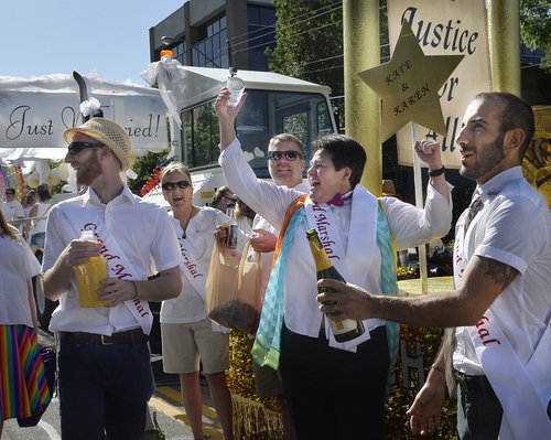 Scott Sommerdorf   |  The Salt Lake Tribune Kate Call, center, raises her glass as Moudi Sbeity, right, pops a bottle of champagne as his spouse, Derek Kitchen, left celebrates with the group at the marriage float just prior to the Salt Lake City Pride Parade, Sunday, June 7, 2014.