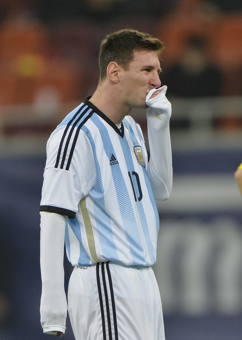 FILE - In this March 5, 2014 file photo, Argentina's Lionel Messi wipes his mouth after appearing to vomit on the pitch during an international friendly soccer game against Romania on the National Arena stadium in Bucharest, Romania. Messi has vomited at least a half-dozen times with Argentina and club team Barcelona, mystifying doctors and fans alike. (AP Photo, File) ROMANIA OUT