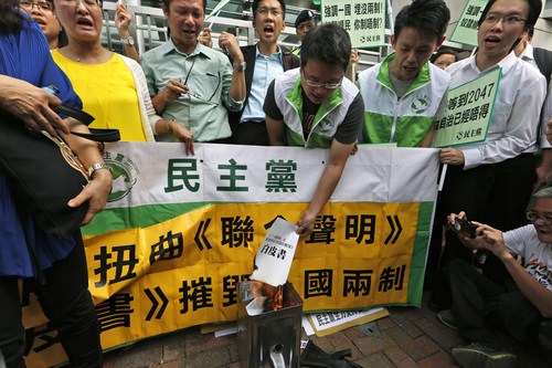 """Protesters burn a mock """"white paper"""" released by Beijing State Council on Tuesday saying it holds ultimate control over the former British colony, outside the Chinese liaison office in Hong Kong, Wednesday, June 11, 2014. The paper was seen as a warning ahead of the protest. Outraged pro-democracy activists reacted by demonstrating in front of the Chinese central government's liaison office, burning copies of the paper. The banner reads """"Distort joint declaration, destroy one country, two system."""" (AP Photo/Kin Cheung)"""