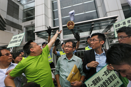 """A protester throws a mock """"white paper"""" released by Beijing State Council on Tuesday saying it holds ultimate control over the former British colony, outside the Chinese liaison office in Hong Kong, Wednesday, June 11, 2014. The paper was seen as a warning ahead of the protest. Outraged pro-democracy activists reacted by demonstrating in front of the Chinese central government's liaison office, burning copies of the paper. The placard reads """"One country, two system missing in one night."""" (AP Photo/Kin Cheung)"""
