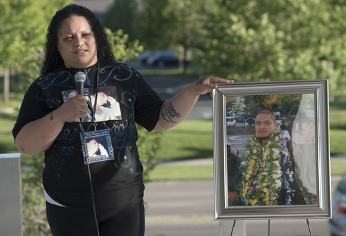 "Steve Griffin  |  The Salt Lake Tribune   Tolina Tausinga, sister of, Siale Angilau, who was shot and killed in the Salt Lake City federal courthouse, places her hand on a portrait of her brother as she speaks during the Justice4Siale Vigil on the courthouse plaza in Salt Lake City, Utah Wednesday, June 11, 2014.  Glendale community members have organized a coalition called ""Raise your Pen Coalition."""