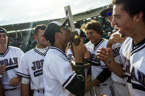 Chris Detrick  |  The Salt Lake Tribune Jordan's Christian Bailey (3) kisses the trophy as he celebrates with their teammates after winning the 5A state championship at Brent Brown Ballpark Friday May 23, 2014. Jordan defeated Pleasant Grove 4-3.