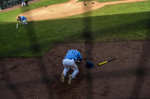 Chris Detrick  |  The Salt Lake Tribune Pleasant Grove's Brayden Cox (20) and Coleman Edwards remain on the ground after the 5A state championship at Brent Brown Ballpark Friday May 23, 2014. Jordan defeated Pleasant Grove 4-3.