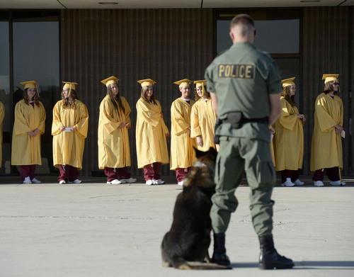Al Hartmann  |  The Salt Lake Tribune A Department of Corrections guard and dog keep order as inmates at the Utah State Prison in Draper enter a buidling for a graduation ceremony to receive their high school diplomas Wednesday June 11, 2014.