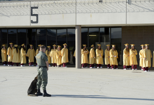 Al Hartmann  |  The Salt Lake Tribune A Department of Corrections guard and dog keep order as inmates at the Utah State Prison in Draper wait for a graduation ceremony to receive their high school diplomas Wednesday June 11, 2014.
