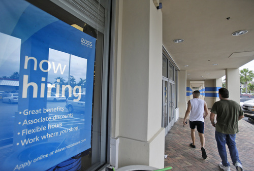 FILE - In this May 16, 2014 file photo, shoppers walk past a now hiring sign at a Ross store in North Miami Beach, Fla. The Labor Department releases weekly jobless claims on Thursday, June 12, 2014. (AP Photo/Wilfredo Lee, File)