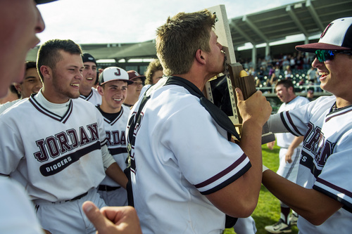 Chris Detrick  |  The Salt Lake Tribune Jordan's Colton Shaver (12) kisses the trophy as he celebrates with their teammates after winning the 5A state championship at Brent Brown Ballpark Friday May 23, 2014. Jordan defeated Pleasant Grove 4-3.