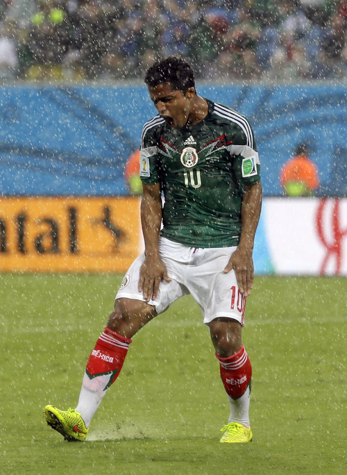 Mexico's Giovani dos Santos reacts after his goal was disallowed during the group A World Cup soccer match between Mexico and Cameroon in the Arena das Dunas in Natal, Brazil, Friday, June 13, 2014.   (AP Photo/Ricardo Mazalan)
