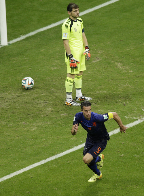 Netherlands' Robin van Persie celebrates running past Spain's goalkeeper Iker Casillas after scoring during the group B World Cup soccer match between Spain and the Netherlands at the Arena Ponte Nova in Salvador, Brazil, Friday, June 13, 2014.  (AP Photo/Christophe Ena)