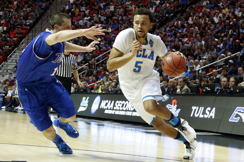 UCLA forward Kyle Anderson, right, drives with the ball as Tulsa forward Lew Evans defends during the first half of a second-round game in the NCAA men's college basketball tournament Friday, March 21, 2014, in San Diego. (AP Photo/Lenny Ignelzi)