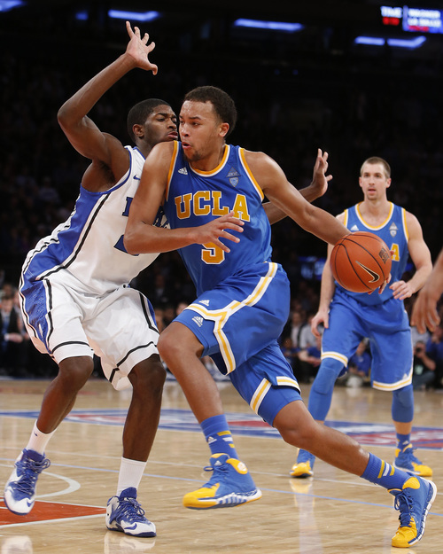UCLA's Kyle Anderson (5) drives against Duke's Amile Jefferson (21) during the second half of an NCAA college basketball game Thursday, Dec. 19, 2013, in New York.  Duke won 80-63. (AP Photo/Jason DeCrow)