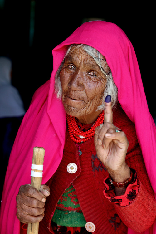 An Afghan woman shows her inked finger after casting her vote at a polling station in Bamiyan, Afghanistan, Saturday, June 14, 2014. Despite Taliban threats of violence, many Afghans vow to cast ballots in Saturday's presidential runoff vote with hopes that whoever replaces Hamid Karzai will be able to provide security and stability after international forces wind down their combat mission at the end of this year. (AP Photo/Kamran Shefayee)