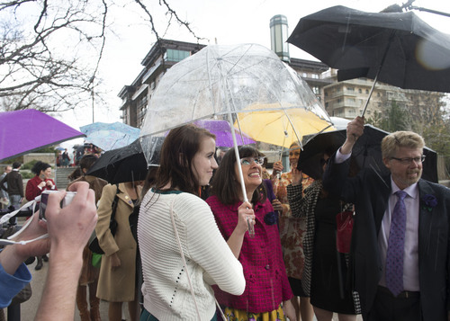Steve Griffin  |  The Salt Lake Tribune   Members and supporters of the Ordain Women, led by Hannah Wheelwright and Kate Kelly, center, brave a hail storm as they walk to the Tabernacle on Temple Square to seek standby tickets to the all-male general priesthood meeting in Salt Lake City, Utah Saturday, April 5, 2014.