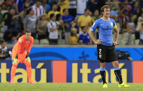 Uruguay's Diego Lugano reacts after Costa Rica scored their third goal during the group D World Cup soccer match between Uruguay and Costa Rica at the Arena Castelao in Fortaleza, Brazil, Saturday, June 14, 2014.    (AP Photo/Bernat Armangue)