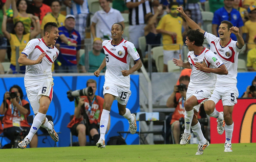Costa Rica's Oscar Duarte, left, celebrates after scoring his side's second goal during the group D World Cup soccer match between Uruguay and Costa Rica at the Arena Castelao in Fortaleza, Brazil, Saturday, June 14, 2014. (AP Photo/Bernat Armangue)
