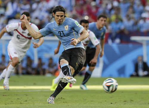 Uruguay's Edinson Cavani (21) kicks a penalty shot to score his side's first goal during the group D World Cup soccer match between Uruguay and Costa Rica at the Arena Castelao in Fortaleza, Brazil, Saturday, June 14, 2014.  (AP Photo/Fernando Llano)