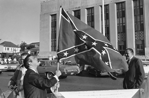 ADVANCE FOR USE SUNDAY, JUNE 15, 2014, AND THEREAFTER - FILE - In this Oct. 9, 1967 file photo, Raymond Roberts, left, raises a large confederate flag on the back of a pickup truck across the street from the federal building in Meridian, Miss. Raymond's brother Alton Wayne Roberts and 17 others went on trial at the federal building on conspiracy charges in the 1964 slaying of three civil rights workers. (AP Photo/File)