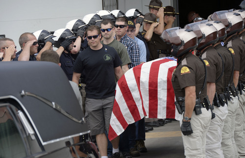 Al Hartmann     The Salt Lake Tribune Family members of slain Las Vegas Police officer Alyn Beck carry his casket through a saluting honor guard of law enforcement officers to a waiting hearse at Salt Lake City International Airport Sunday June 15, 2014.  The hearse and family were escorted to the Wyoming border along I-80 by an honor guard of Idaho and Utah motorcycle patrolmen.
