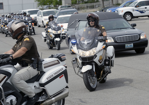 Al Hartmann     The Salt Lake Tribune An honor guard of Idaho and Utah motorcycle patrolmen escort the hearse of slain Las Vegas Police Officer Alyn Beck from Salt Lake City International Airport to the Wyoming state line Sunday June 15, 2014. He is to be buried in Afton, Wyoming.