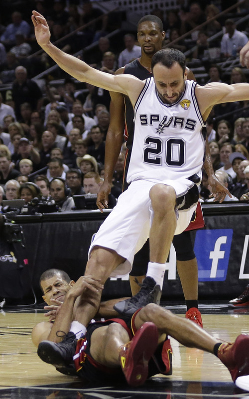 San Antonio Spurs guard Manu Ginobili (20) tumbles over Miami Heat forward Shane Battier during the first half in Game 5 of the NBA basketball finals on Sunday, June 15, 2014, in San Antonio. (AP Photo/David J. Phillip)