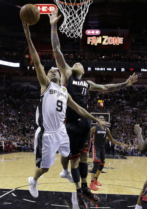 San Antonio Spurs guard Tony Parker (9) shoots as Miami Heat forward Chris Andersen defends during the first half in Game 5 of the NBA basketball finals on Sunday, June 15, 2014, in San Antonio. (AP Photo/David J. Phillip)