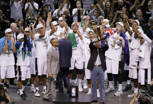 San Antonio Spurs owner Peter Holt holds up the Larry O'Brien NBA Championship Trophy after Game 5 of the NBA basketball finals against the Miami Heat on Sunday, June 15, 2014, in San Antonio. The Spurs won the NBA championship 104-87. (AP Photo/Tony Gutierrez)