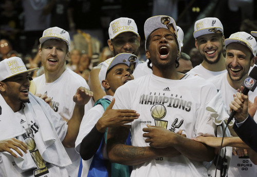 Most Valuable Player San Antonio Spurs forward Kawhi Leonard, third from right, celebrates after Game 5 of the NBA basketball finals against the Miami Heat on Sunday, June 15, 2014, in San Antonio. The Spurs won the NBA championship 104-87. (AP Photo/David J. Phillip)