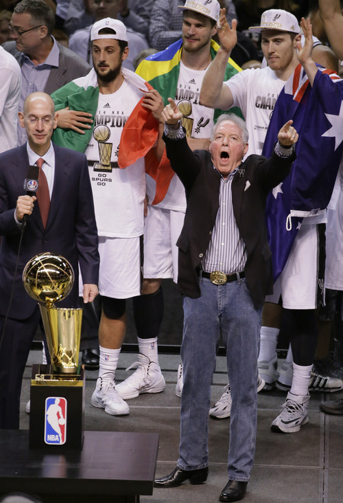 San Antonio Spurs owner Peter Holt celebrates with the team before receiving the Larry O'Brien NBA Championship Trophy after Game 5 of the NBA basketball finals against the Miami Heat on Sunday, June 15, 2014, in San Antonio. The Spurs won the NBA championship 104-87. (AP Photo/Tony Gutierrez)