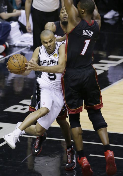 San Antonio Spurs guard Tony Parker (9) passes the ball against Miami Heat center Chris Bosh (1) during the first half in Game 5 of the NBA basketball finals on Sunday, June 15, 2014, in San Antonio. (AP Photo/Tony Gutierrez)