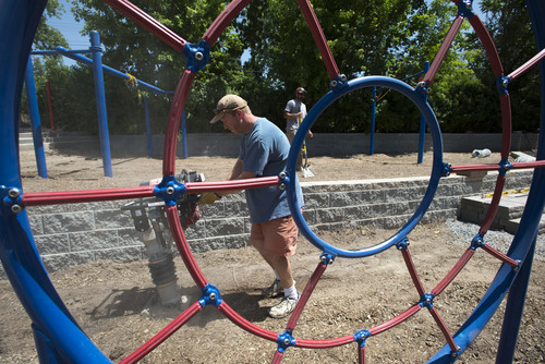 Steve Griffin  |  The Salt Lake Tribune   Charles Van Wagoner, left, and Trevor Hoyles work on a new playground at Holladay United Methodist Church in Holladay on Friday, June 13, 2014. Van Wagoner and Hoyles are getting help from dozens of other dads on the project.