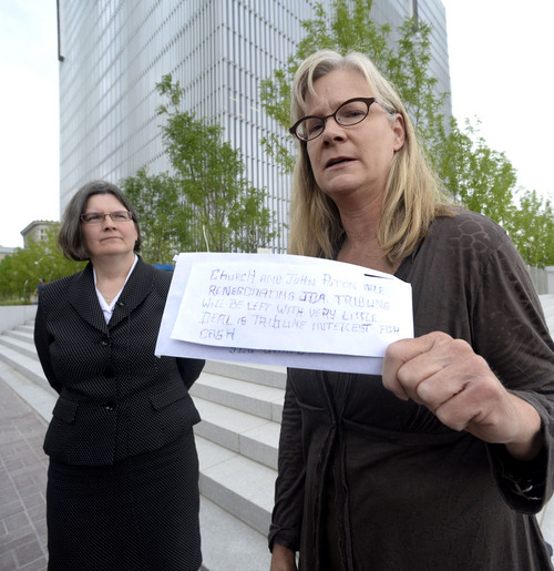 Al Hartmann  |  The Salt Lake Tribune Former Tribune staffer Joan O'Brien, right,  with lawyer Karra Porter pause on the steps of the Federal Courthouse in Salt Lake City Monday June 16 after filing an injunction in U.S District Court seeking an injunction blocking the paper's new profit-sharing split and other key provisions of the partnership with the Deseret News.   She holds an anonymous letter sent to reporters at the Tribune before the change of the profit sharing split was changed.
