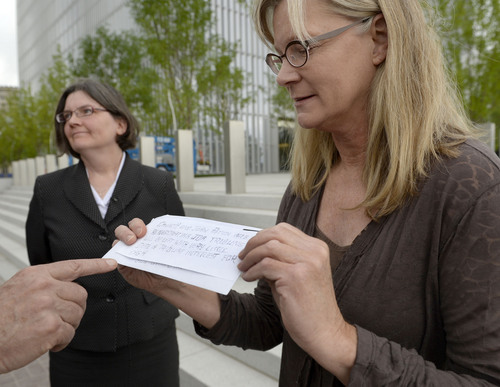 Al Hartmann  |  The Salt Lake Tribune Former Tribune staffer Joan O'Brien with lawyer Karra Porter pause on the steps of the Federal Courthouse in Salt Lake City Monday June 16 after filing an injunction in U.S District Court seeking an injunction blocking the paper's new profit-sharing split and other key provisions of the partnership with the Deseret News.   She holds an anonymous letter sent to reporters at the Tribune before the change of the profit sharing split was changed.