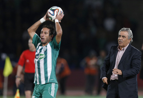 Raja Casablanca's Coach Faouzi Benzarti, right, looks at Raja Casablanca's Adil Karrouchy as he throws the ball during the semi final soccer match between Raja Casablanca and Atletico Mineiro at the Club World Cup soccer tournament in Marrakech, Morocco, Wednesday, Dec. 18, 2013. (AP Photo/Christophe Ena)