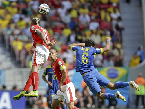 Switzerland's Valon Behrami, left, beats Ecuador's Cristhian Noboa to win a header during the group E World Cup soccer match between Switzerland and Ecuador at the Estadio Nacional in Brasilia, Brazil, Sunday, June 15, 2014. (AP Photo/Martin Mejia)