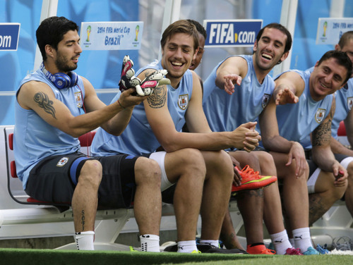 Uruguay's players, from left, Luis Suarez, Sebastian Coates, Abel Hernandez, partially covered, Diego Godin, and Cristian Rodriguez joke prior a training session at Arena Castelao in Fortaleza, Brazil, Friday, June 13, 2014. Uruguay will play a World Cup game on June 14. (AP Photo/Fernando Llano)