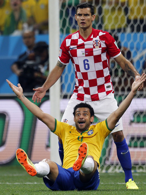 Brazil's Fred, bottom, raises his arms after a penalty was called against Croatia's Dejan Lovren, top, by referee Yuichi Nishimura, from Japan, during the group A World Cup soccer match between Brazil and Croatia in the opening game of the tournament at the Itaquerao Stadium in Sao Paulo, Brazil, Thursday, June 12, 2014. Brazil was issued a penalty kick following the play leading to a goal by Neymar helping Brazil to a 3-1 victory. (AP Photo/Frank Augstein)