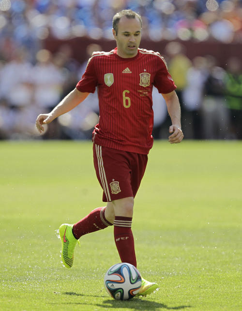 In this June 7, 2014 photo, Spainís Andres Iniesta wears his Nike Magista cleats during an exhibition soccer game against El Salvador, in Landover, Md. Nike, Adidas and Puma are all trotting out new looks and innovation in footwear for this summerís World Cup. The result will be a clash of colors when the teams take the field in Brazil.  (AP Photo/Luis M. Alvarez)