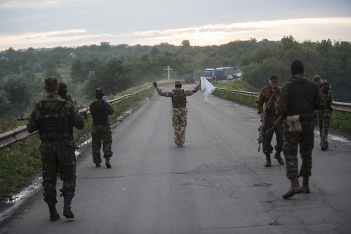 Pro-Russian fighters wave a white flag to start a handover of the bodies of Ukrainian troops killed in a plane shot down near Luhansk, at a check point in the village of Karlivka near Donetsk, eastern Ukraine, Wednesday, June 18, 2014. The two sides managed to arrange a brief truce Wednesday evening in the eastern town of Karlivka to allow pro-Russian forces to hand over the bodies of 49 Ukrainian troops who died when the separatists shot down a transport plane bound for the airport in Luhansk last weekend.  (AP Photo/Evgeniy Maloletka)