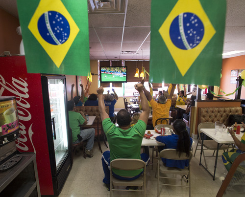 Steve Griffin  |  The Salt Lake Tribune Packed into Bakery Street bakery in Salt lake City, Brazil fans celebrate Neymar's first goal during their game against Croatia, kicking off the World Cup in Brazil on Thursday.