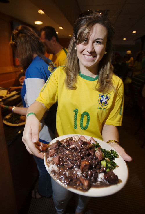 Steve Griffin  |  The Salt Lake Tribune   Transplanted Brazilian, Beatriz Goncalvez, holds a plate of Feijoada, the national dish of Brazil as she attends a World Cup soccer party at Rodizio Grill in Salt Lake City on Thursday, June 12, 2014. Feijoada is a stew made with beans and pork and served over rice. Included on her plate is collard greens, sausage, chicken hearts and ground yuca root.