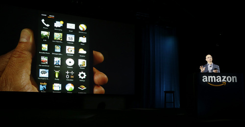 Amazon CEO Jeff Bezos shows off the app grid on the new Amazon Fire Phone at a launch event, Wednesday, June 18, 2014, in Seattle. (AP Photo/Ted S. Warren)