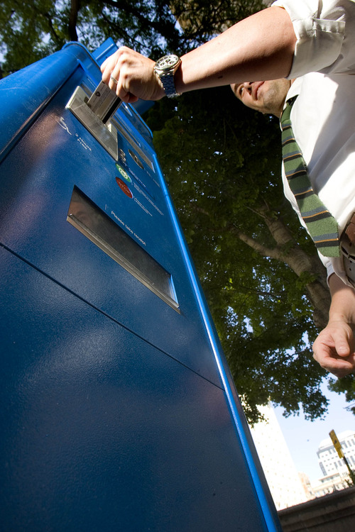 Paul Fraughton  |   The Salt Lake Tribune Chad Golsan, of Salt Lake City, inserts a credit card into a parking kiosk on Main Street. A lawsuit filed against the city claims city code wasn't changed to authorize procedural changes that came with the meters.