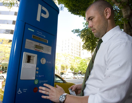 Paul Fraughton  |   The Salt Lake Tribune Chad Golsan, of Salt Lake City, goes through the steps to pay for parking at a parking kiosk on Main Street Wednesday, August 21, 2013. A lawsuit filed against the city claims city code wasn't changed to authorize procedural changes that came with the meters.