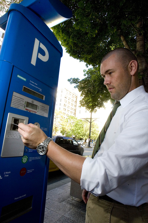 Paul Fraughton  |   The Salt Lake Tribune Chad Golsan, of Salt Lake City, goes through the steps to pay for parking at a  parking kiosk on Main Street.  A lawsuit filed against the city claims city code wasn't changed to authorize procedural changes that came with the meters.