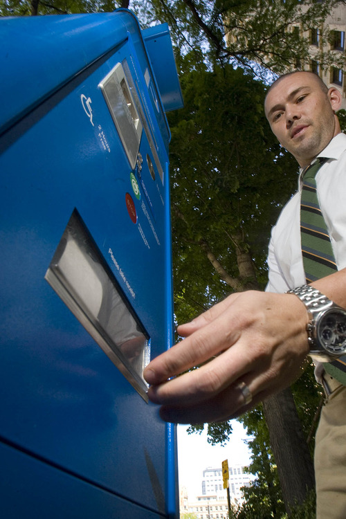 Paul Fraughton  |   The Salt Lake Tribune Chad Golsan, of Salt Lake City, reaches for his parking receipt from  a parking kiosk on Main Street Wednesday, August 21, 2013. A lawsuit filed against the city claims city code wasn't changed to authorize procedural changes that came with the meters.