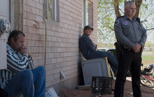 In this April 20, 2006, photo, Taylor Bistline occupys the doorway of a disputed home in an effort to prevent his brother, Patrick Pipkin, (not pictured) from entering while their brother Wendell Pipkin and Colorado City Police Officer Helaman Barlow await the arrival of Attorney Jeff Sheilds. Photo by Todd Chamberlin