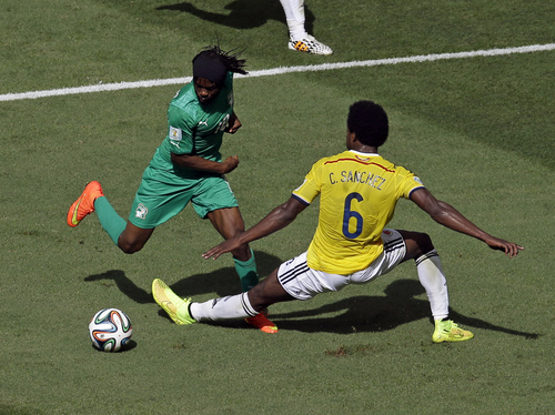 Ivory Coast's Gervinho dribbles past Colombia's Carlos Sanchez Moreno before scoring during the group C World Cup soccer match between Colombia and Ivory Coast at the Estadio Nacional in Brasilia, Brazil, Thursday, June 19, 2014.  (AP Photo/Themba Hadebe)