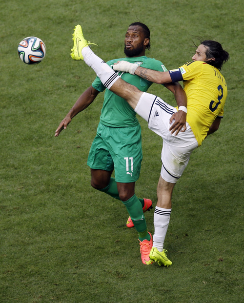 Ivory Coast's Didier Drogba  fights for the ball with Colombia's Mario Yepes during the group C World Cup soccer match between Colombia and Ivory Coast at the Estadio Nacional in Brasilia, Brazil, Thursday, June 19, 2014.  (AP Photo/Themba Hadebe)