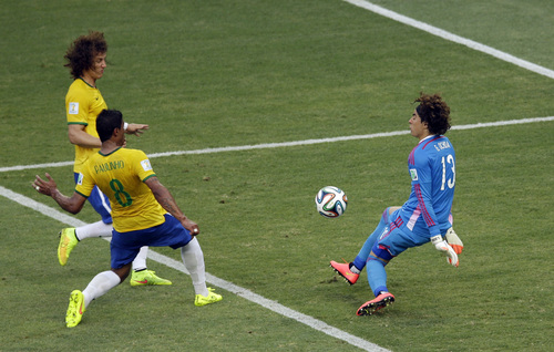 Mexico's goalkeeper Guillermo Ochoa, right, deflects a ball as Brazil's David Luiz, left, and  Paulinho approach during the group A World Cup soccer match between Brazil and Mexico at the Arena Castelao in Fortaleza, Brazil, Tuesday, June 17, 2014.  (AP Photo/Themba Hadebe)